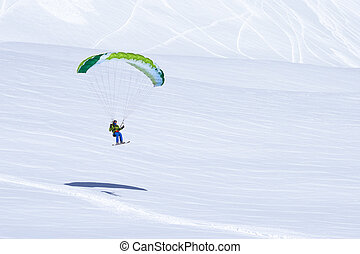 green skier finish with a paraglider - green skier finish...