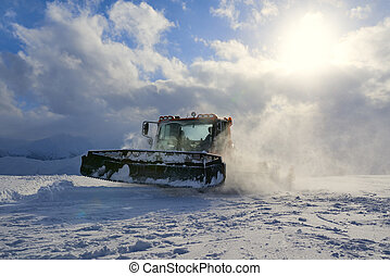 snowcat evening working on a slope - snowcat works on a...