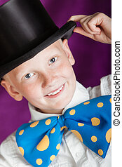 Handsome dapper little boy in a top hat and enormous blue...
