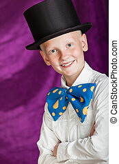 Handsome dapper young boy in a top hat and huge colorful...