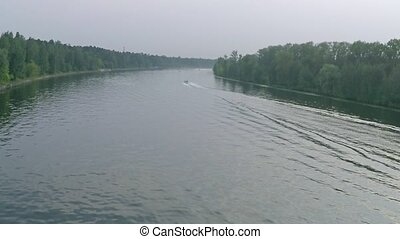 Aerial video of a boat cruising along big forest river -...