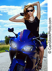 girl on her motorcycle - Attractive woman biker posing on...