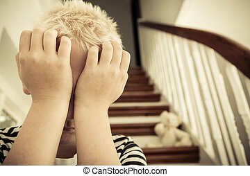 Close up of child with hands against his face sits in...