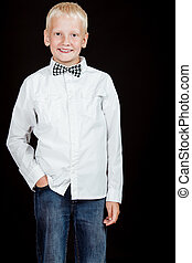 Boy standing with one hand in pocket smiles at camera while...