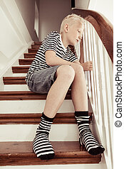 Blond boy wearing stripped shirt and socks stares sadly as...