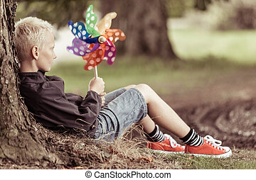 Blond boy holding colorful whirligig sits by tree while...