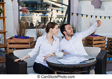 Happy business couple taking selfie at outdoor restaurant