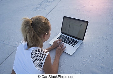 Pretty blonde woman with laptop computer on a rooftop
