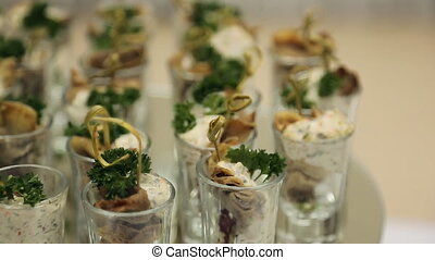 Cold snacks in a glass cup with cream and herbs, blur. Many...