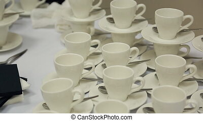 White cups with saucers and teaspoons are on table in...