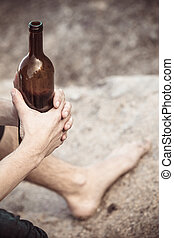 Male hand with wine bottle outdoor - Man depressed holding...