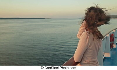 Young pretty woman on cruise ship at sunset.