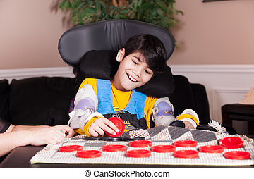 Young disabled boy in wheelchair playing checkers - Young...