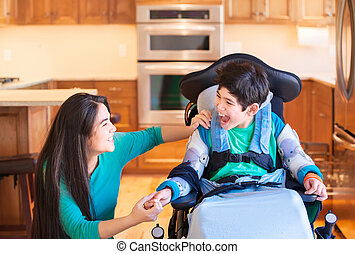 Disabled boy in wheelchair laughing with teen sister in...