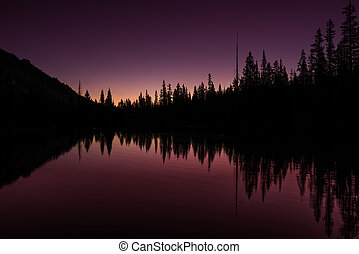 Idaho mountain lake first light colored sky and reflection -...