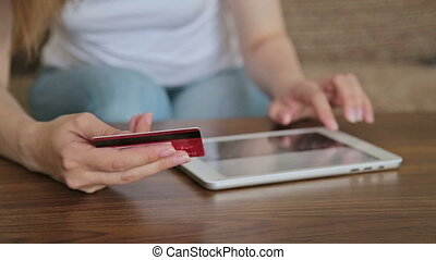 Woman's hands typing security code from credit card - Female...