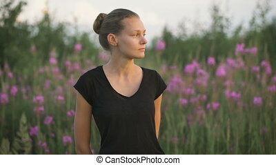Beautiful young healthy woman standing at a green field and...