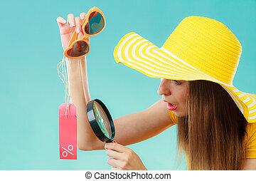 woman choosing glasses searching through magnifying glass -...