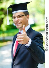 Happy graduateing student wearing graduation hat ans showing...
