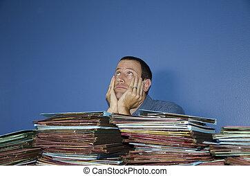 Overworked employee - Man hiding behind piles files looking...