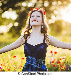Beautiful young woman on the poppy field in sunlight