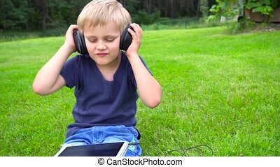 boy listen music on tablet outdoors
