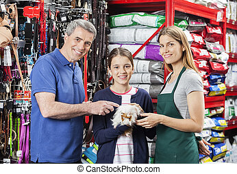 Girl Holding Guinea Pig With Father And Saleswoman In Store...