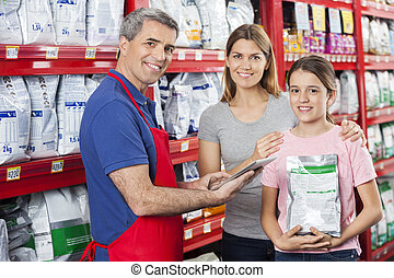 Salesman Assisting Family In Buying Pet Food At Store -...