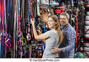 Happy Couple Buying Leash At Pet Store - Side view portrait...