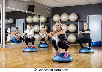 Woman Doing Squatting Exercise On Bosu Ball With Friends -...