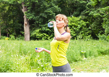 Fitness woman drinking water from bottle. Muscular young...