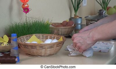 hands put white egg into material and boil in pot. Easter eggs painting.