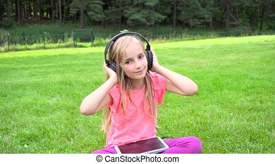 girl listen music on tablet outdoors - cute girl listen...