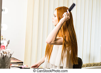 Health beauty and haircare concept - Young woman refreshing her hairstyle she combing long red hair with comb
