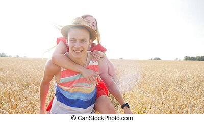 Young, happy couple have a piggy back in the field - Young,...