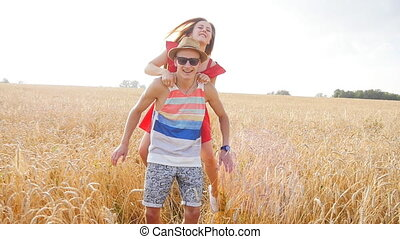 Young, happy couple have a piggy back in the field