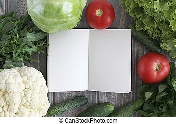 Note book and composition of vegetables on grey wooden desk....