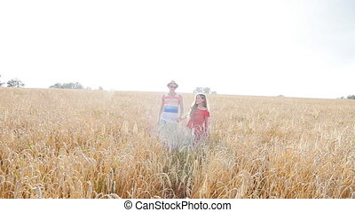 Happy young couple walking together through wheat field...