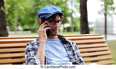 man calling by smartphone sitting on street bench 48 -...