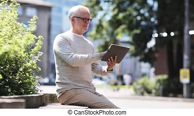 senior man with tablet pc on city street - technology,...