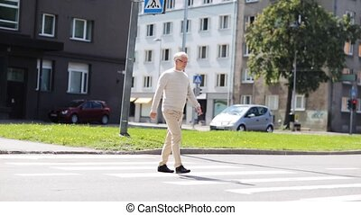 senior man walking along city crosswalk - leisure and people...