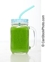 Jar tumbler mug with green smoothie drink over white