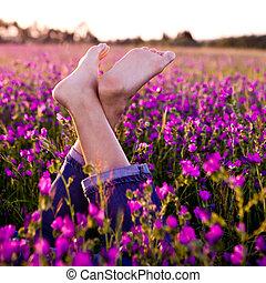 Crossed legs - Female crossed legs on a beautiful flowery...