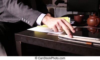Businessman sitting office desk signs a bill comparing them, with the pc tablet. close-up hands of a man and a fountain pen