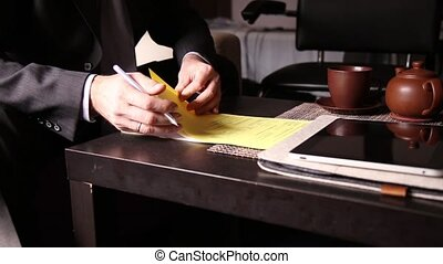 Businessman sitting office desk signs a bill comparing them,...