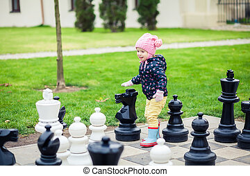 girl playing with giant chess