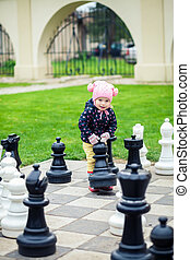 cute little girl playing with giant chess