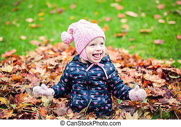 happy little girl laughing in the autumn park
