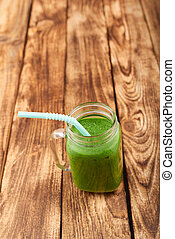 Jar tumbler mug with green smoothie drink over wooden...