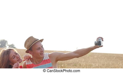 Young couple making selfie outdoors at field